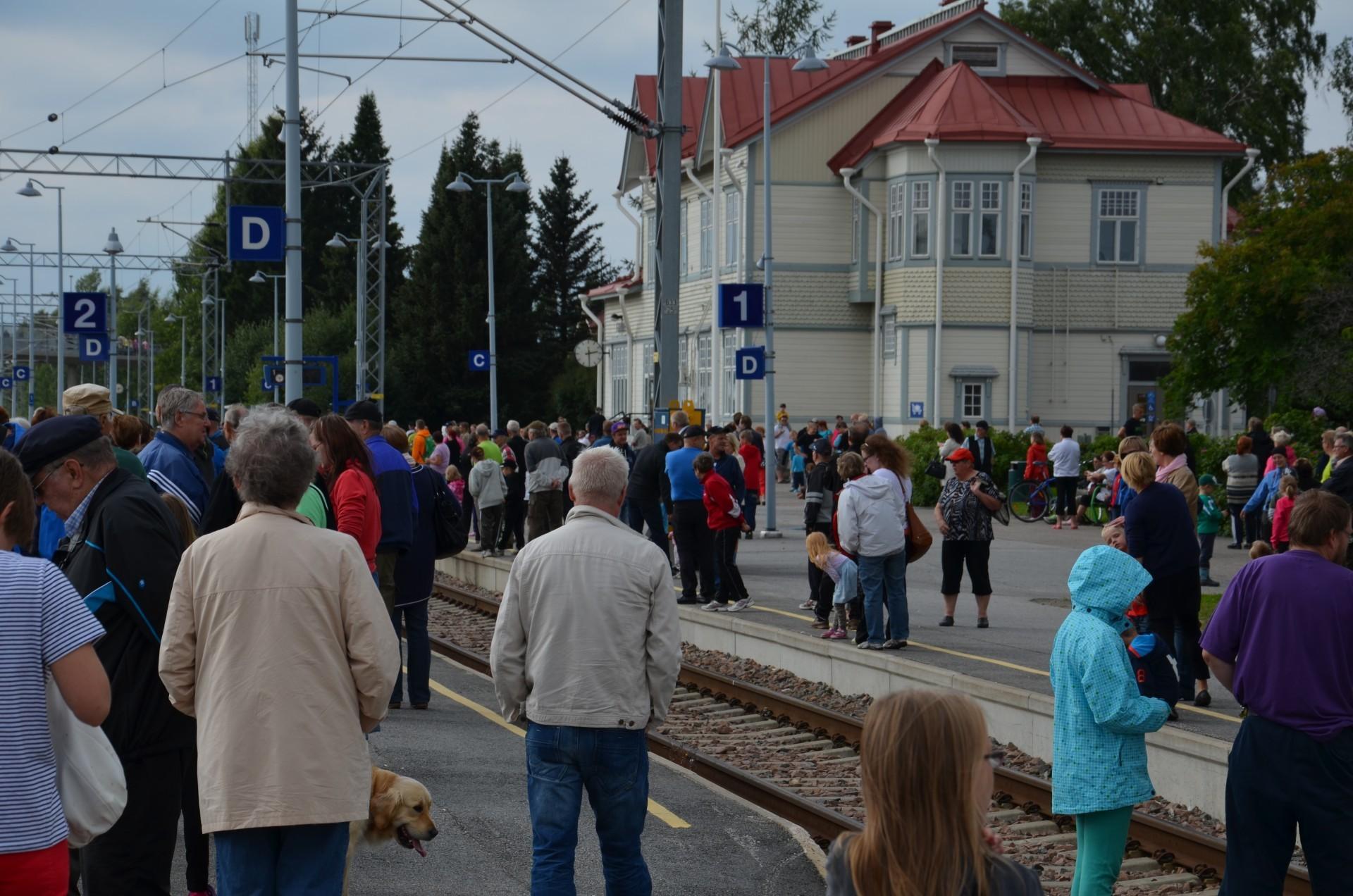 Kajaanilaiset odottavat sankoin joukoin rautatieasemalle saapuvaa höyryveturia 17.8.2013.