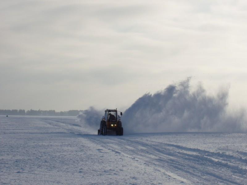 Traktori linkoaa lunta Paltaselän jäätieltä helmikuussa 2005.